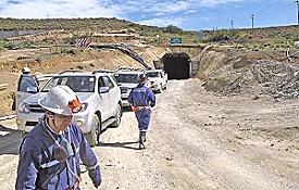 Mineros y vehículos de Minera Santa Cruz, al fondo uno de los túneles del yacimiento.
